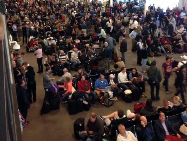 Pasajeros esperan en la Terminal Internacional Tom Bradley del Aeropuerto Internacional de Los Ángeles, donde miles de vuelos están retrasados después de un tiroteo.