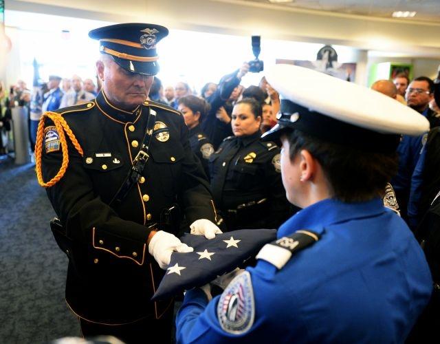 El oficial de policía de LAX Tom Dye pasa a la Bandera de Honor de EEUU a la  guardia de honor Brandy Richards, de TSA, en el Aeropuerto Internacional de Los Ángeles, en un acto en memoria de del agente de TSA Gerardo Hernández.