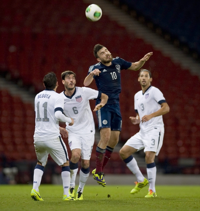 El escocés Robert Snodgrass cabecea  la pelota entre Alejandro Bedoya (izq.) Brad Evans  y Omar González de Estados Unidos.
