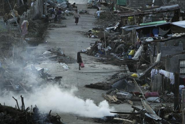 Víctimas del tifón en Filipinas caminan entre los escombros de la localidad de Basey, en la provincia de la Isla Samar. La búsqueda de los desaparecidos, 1,179 según el recuento oficial, es una situación infernal para muchos en Filipinas.