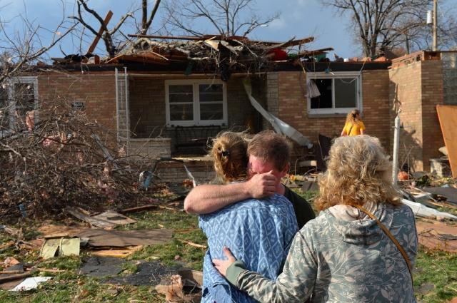Ray Baughman abraza a su familia llorando momentos despues que vio  su casa destruida por uno de los tornados que afectó New Minden, en  Illinois. Muchos como él y su familia, deberán asistir a refugios donde permanecer por algún tiempo.