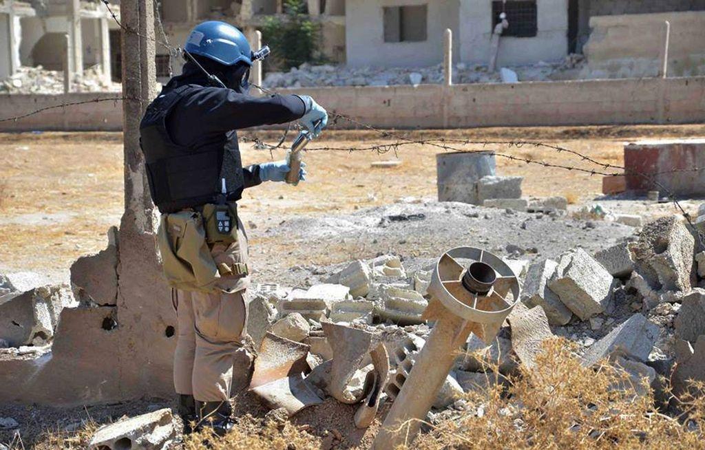 Miembros del grupo investigativo de las Naciones Unidas toman muestras de arena cerca de una zona impactada por misiles en Damasco.