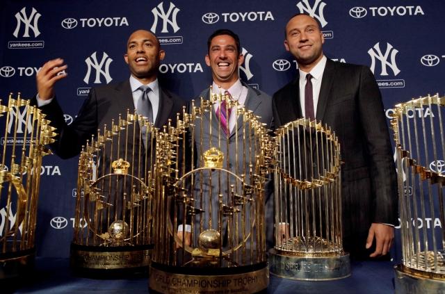 Rivera (izq.), Posada y Jeter, con los cuatro trofeos de la Serie Mundial, todos, bajo el mandato del ahora inmortal Joe Torre.