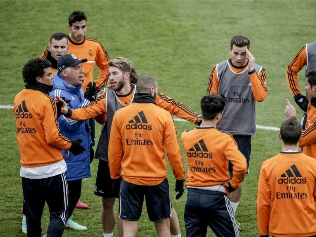 El técnico del Real Madrid, Carlo Ancelotti, rodeado de jugadores durante el último entrenamiento de 2013 del equipo celebrado hoy al calor de sus aficionados en el estadio Alfredo Di Stéfano que registró un lleno en sus gradas