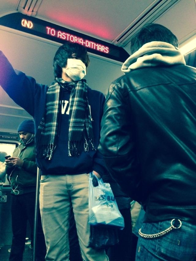 Un pasajero del tren N, en Astoria, se cubre la boca para evitar ser contagiado.