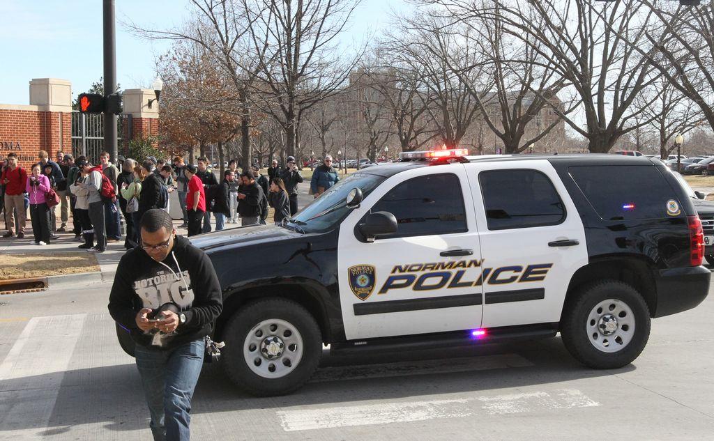 Un grupo de estudiantes se congrega en la calle Lindsey en las afueras de la Universidad de Oklahoma, luego de recibir el mensaje de texto alertando de un tiroteo.