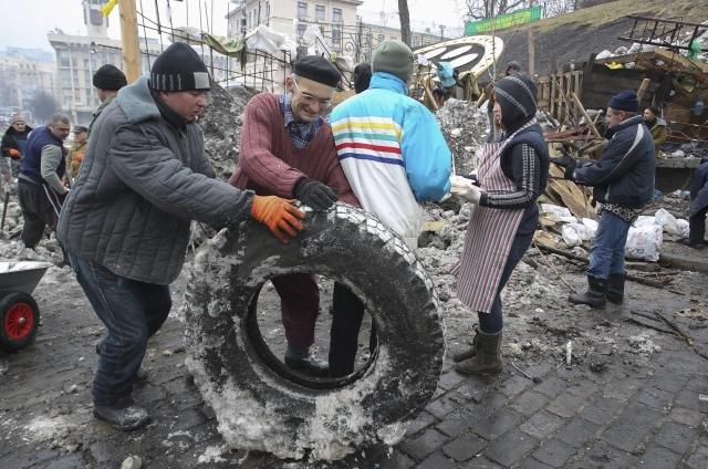 Varios manifestantes trasladan un neumático junto a una barricada en la Plaza de la Independencia de Kiev (Ucrania), ayer.