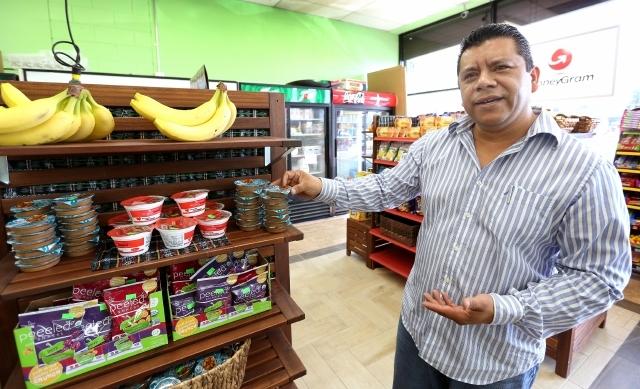 Nelson García muestra la nueva sección de su tienda de abarrotes, donde coloca plátanos, frutos secos, barras naturales de granos y otros productos frescos y saludables.
