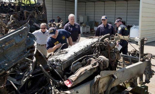 Foto proveída por las autoridades muestra a investigadores del Consejo Nacional de Seguridad Vial (NTSB) examinando los restos del camión de FedEx.