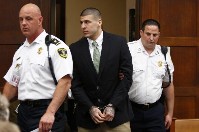 BOS282. BOSTON (MA, EE.UU.), 28/05/2014.- El exjugador de fútbol americano Aaron Hernández (c) es llevado a una audiencia del juicio que se le sigue por homicidio hoy, miércoles 28 de mayo de 2014, en la Corte Superior de Suffolk, en Boston, Massachusetts (EE.UU.). Hernández está acusado de emboscar y asesinar a dos hombres en 2012 después de un altercado en un club nocturno de Boston. El exjugador, además, enfrenta cargos separados por el asesinato en 2013 del jugador semiprofesional Odin Lloyd. EFE/Dominick Reuter/POOL