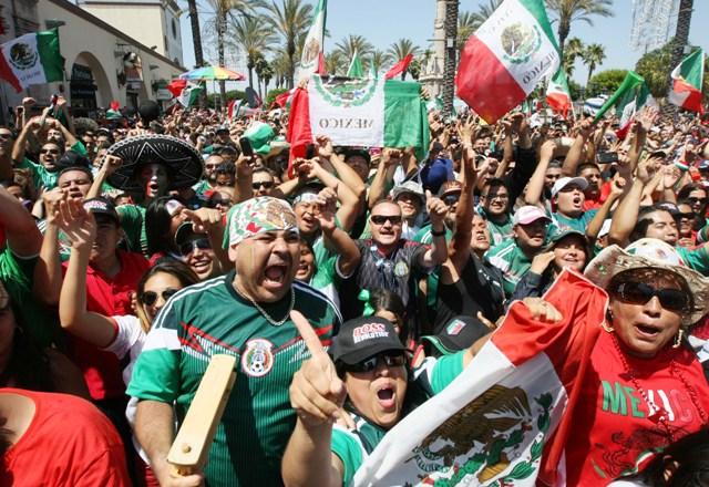 Aficionados mexicanos celebran un gol en la Plaza México de Lynwood.