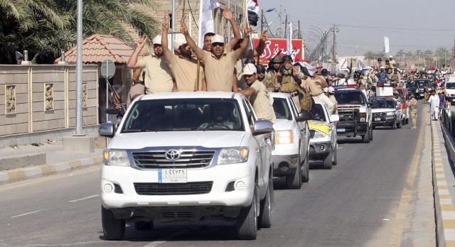 Voluntarios chiítas reclutados para luchar contra las fuerzas de seguridad iraquíes gritan eslóganes.