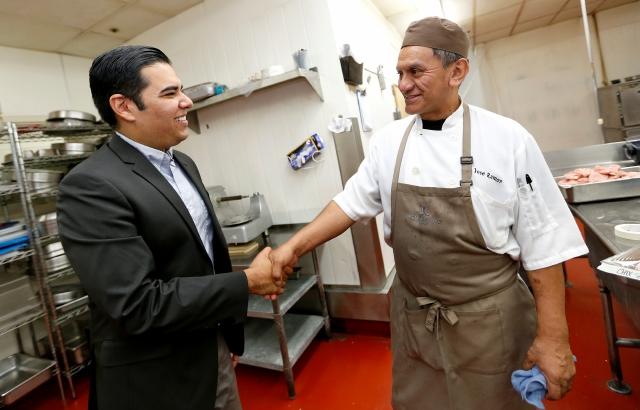 Robert García estrecha la mano del chef José Ramón Gandarilla en un hotel de Long Beach. García  será el alcalde más joven de Long Beach, el primero abiertamente gay y el primer latino.