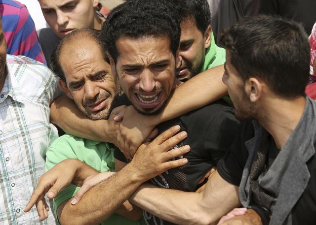Los parientes de siete miembros de una misma familia, con doble nacionalidad palestina y alemana, se abrazan durante el funeral por sus seres queridos  en la ciudad de Beit Lahiya.