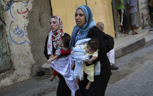Mujeres palestinas con sus hijos en brazos salen de sus casas y buscan refugio durante uno de los ataques aéreos israelíes sobre la ciudad de Gaza.