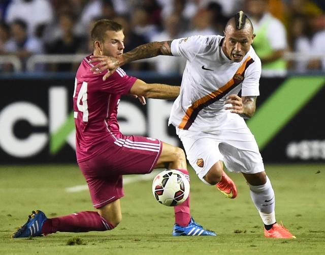 El jugador del Real Madrid Asier Illarramendi (izq.) es desbordado por  Radja Nainggolan  de la Roma.