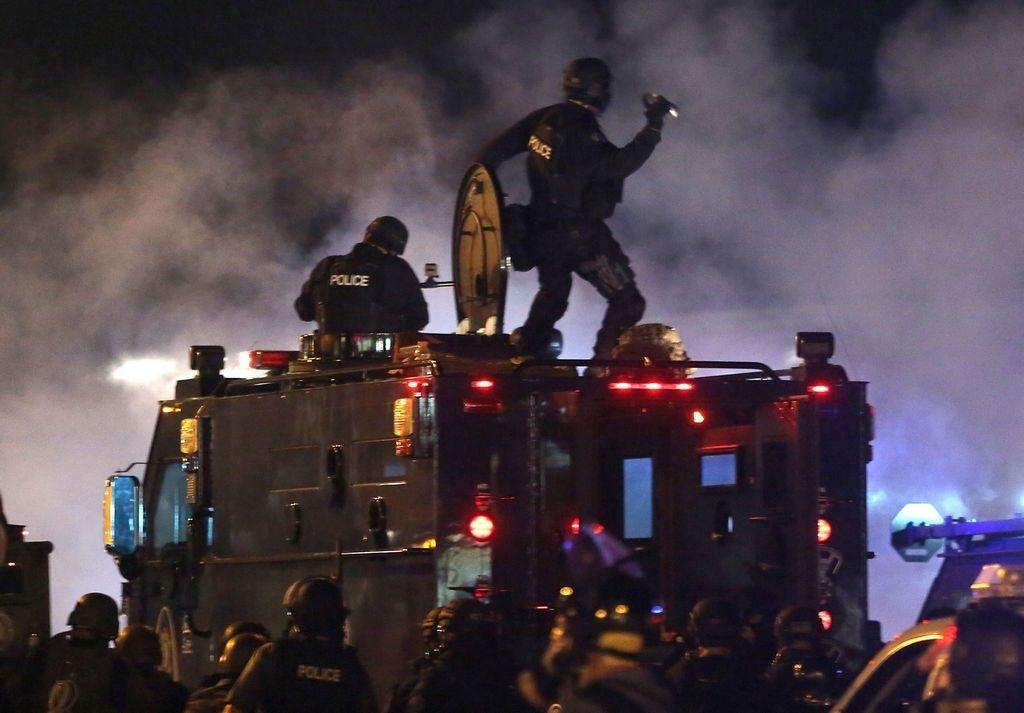 Un agente policíaco de Ferguson apunta a la multitud de protestantes con botes de gas lacrimógeno en la mano.