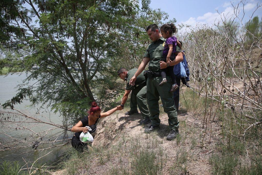 Agentes de la Patrulla Fronteriza ayudan a salir del Río Bravo a una  mujer con su hija, que han llegado ilegalmente a EEUU.