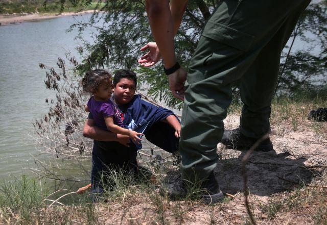 Un agente de la Patrulla Frontera ayuda a inmigrantes que cruzaron el Río Bravo, en Texas, el 24 de julio de 2014.