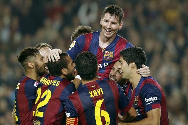 Lionel Andrés Messi (arriba) al momento de ser felicitado por sus compañeros tras el partido de Liga ante el Sevilla FC, en el que se convirtió  en el máximo goleador de la historia de la Liga.