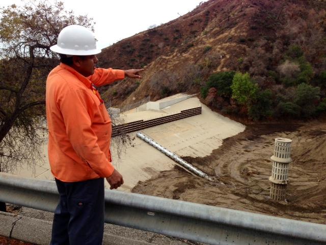 Paul Nieto, operador de maquinaria pesada del Departamento de Obras Públicas del condado de Los Ángeles, señala el área que desde el jueves pasado han limpiado por los deslaves en una montaña de Glendora incendiada hace unos meses.