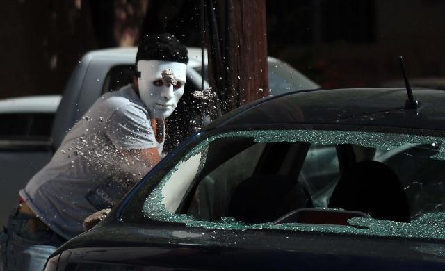 Un hombre enmascarado destruye automóviles al frente del edificio de la fiscalía en  Chilpancingo,  Guerrero