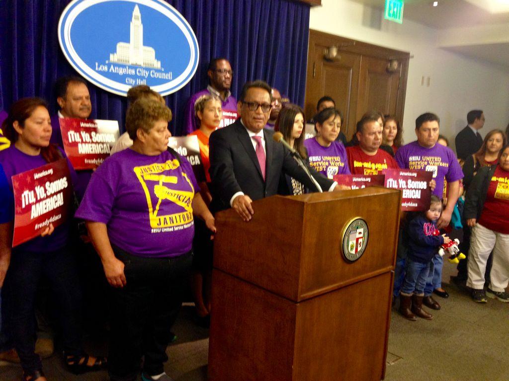 El concejal de Los Ángeles, Gil Cedillo, rodeado por inmigrantes, cuenta los detalles de la defensa por los alivios migratorios.