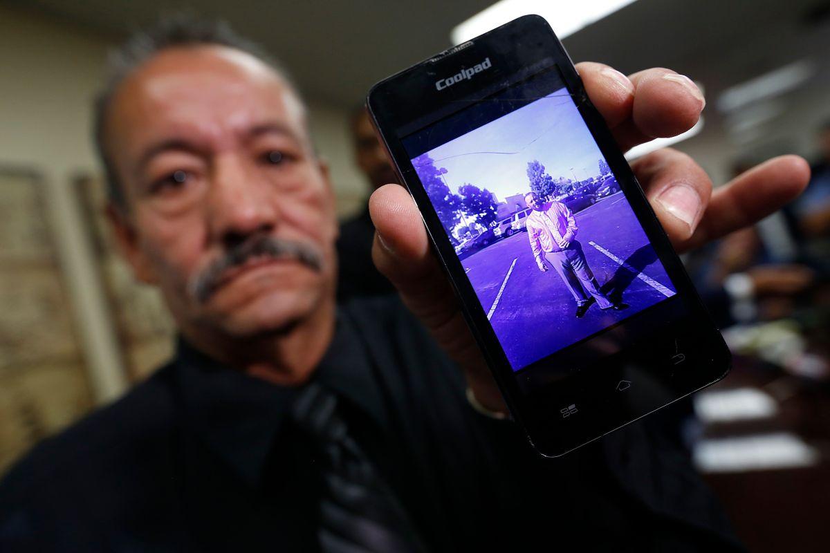 El padre muestra una foto familiar de su hijo, que él cree murió a consecuencias de las descargas eléctricas que le propinaron los agentes del Sheriff. / AURELIA VENTURA