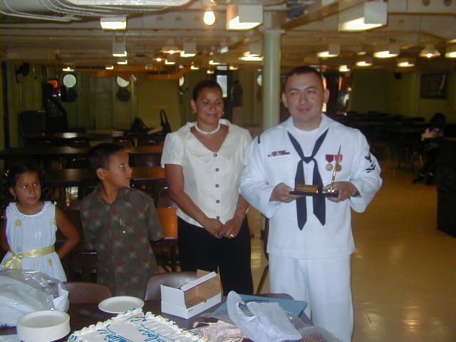 Carlos con su uniforme de la marina y en compañía de sus dos hijos y su esposa.