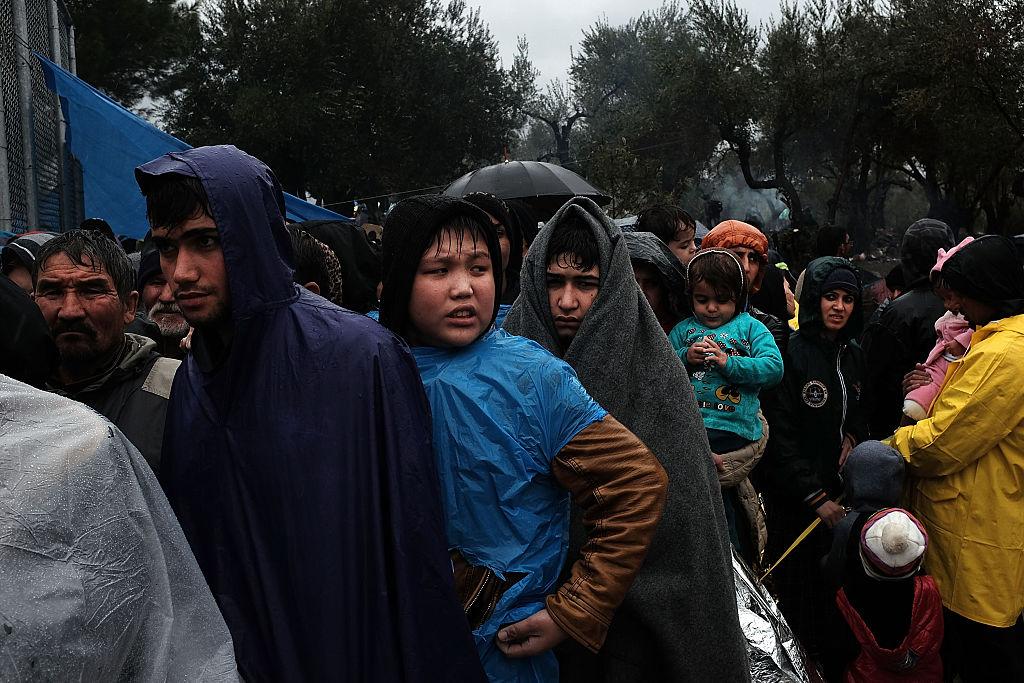 Refugiados bajo la lluvia en un campamento superpoblado en la isla de Lesbos, en Grecia.
