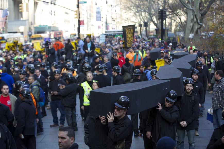 Los trabajadores cargaron 16 ataúdes negros por las calles que rodean a la Alcaldía.