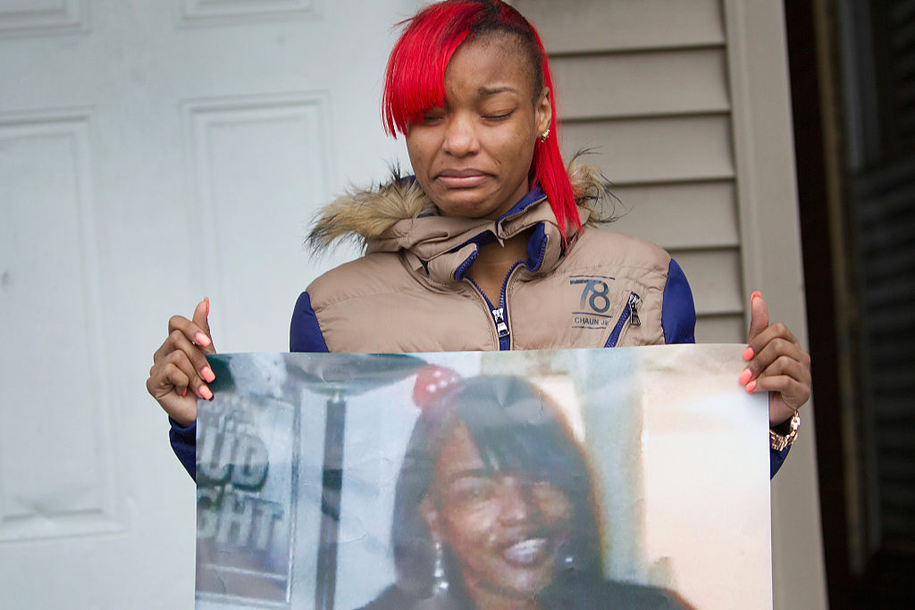 LaTonya Jones, hija de  Bettie Jones sostiene una fotografía de su madre durante una vigilia afuera de su casa, el 27 de diciembrte de 2015 en Chicago.
