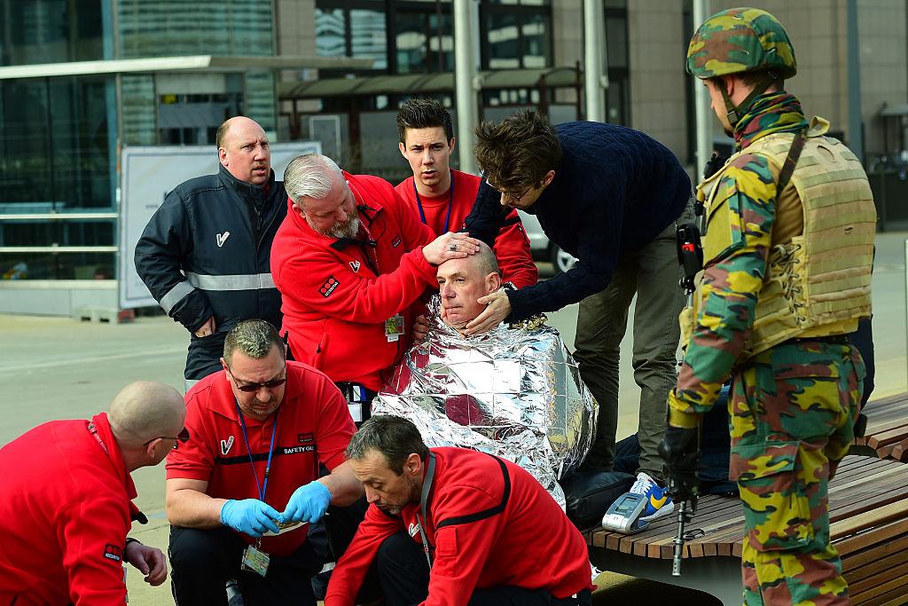 Víctima recibe primeros auxilios de rescatistas cerca de la estación del metro de Maalbeek en Bruselas, tras el atentado a esta estación cercana a los edificios de la Unión Europea que causó varias muertes y centenares de heridos.