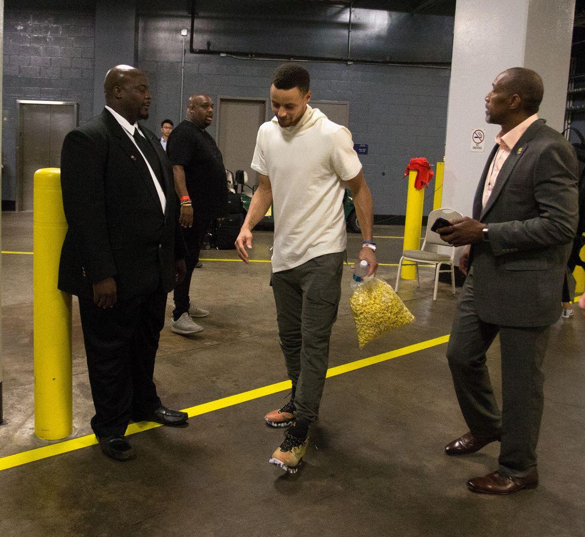 Stephen Curry abandona lentamente la arena de los Rockets de Houston tras el juego que Golden State ganó el domingo y en el que el astro sufrió una lesión de la rodilla derecha.