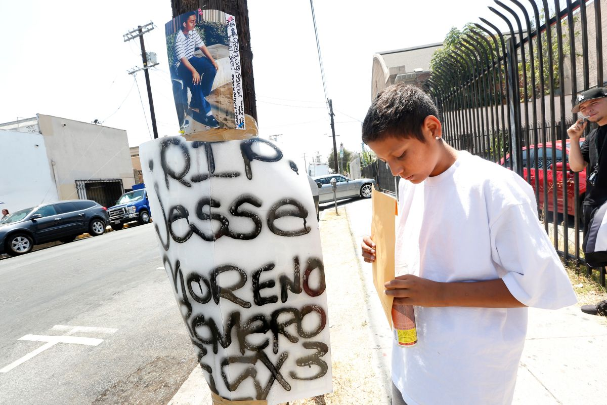 Richard Romero, hermano menor de Jesse Romero, coloca velas en el altar erguido en honor a su hermano mayor. (Aurelia Ventura/ La Opinion)