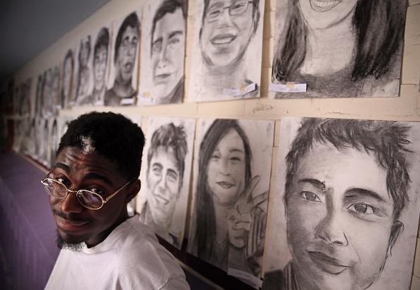 Phillip Sossou junto a algunos de los retratos que dibujó.