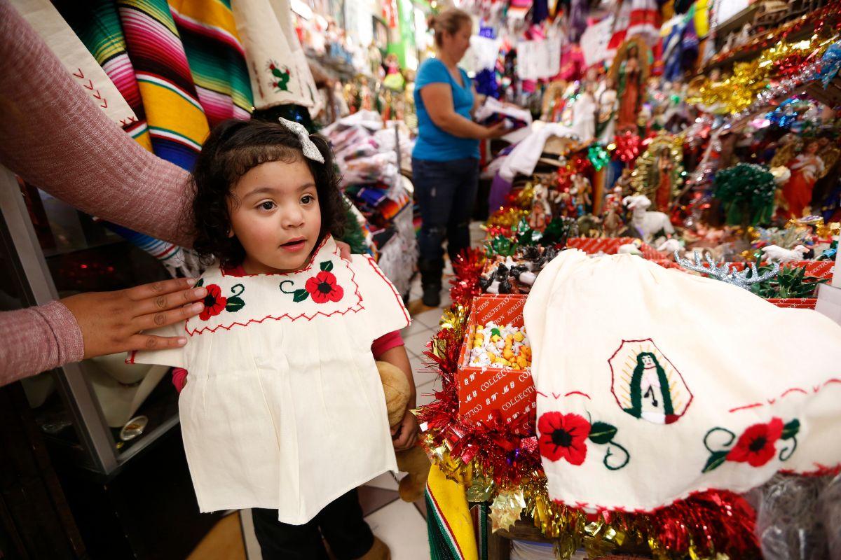 La pequeña de 2 años Rosemary Sandoval se prueba un traje en el popular  Mercadito del Este de Los Ángeles.