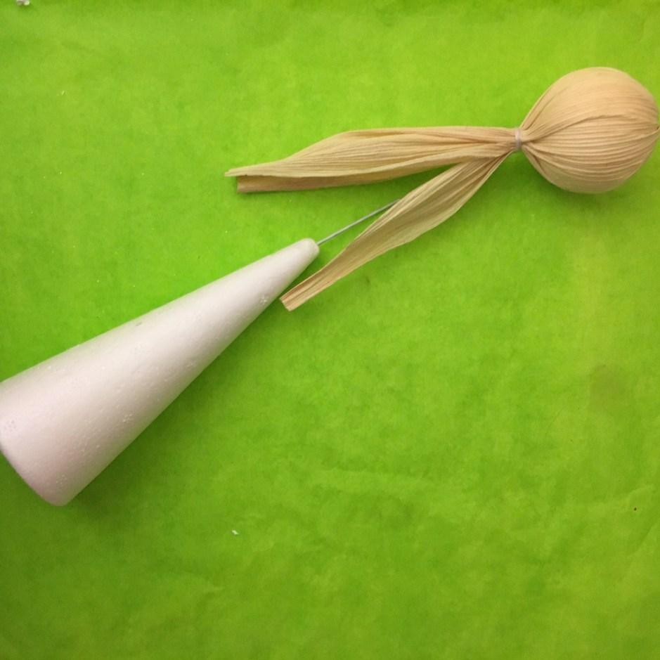 Con un pedazo de alambre se une el cono de unicel a lo que será la cabeza.