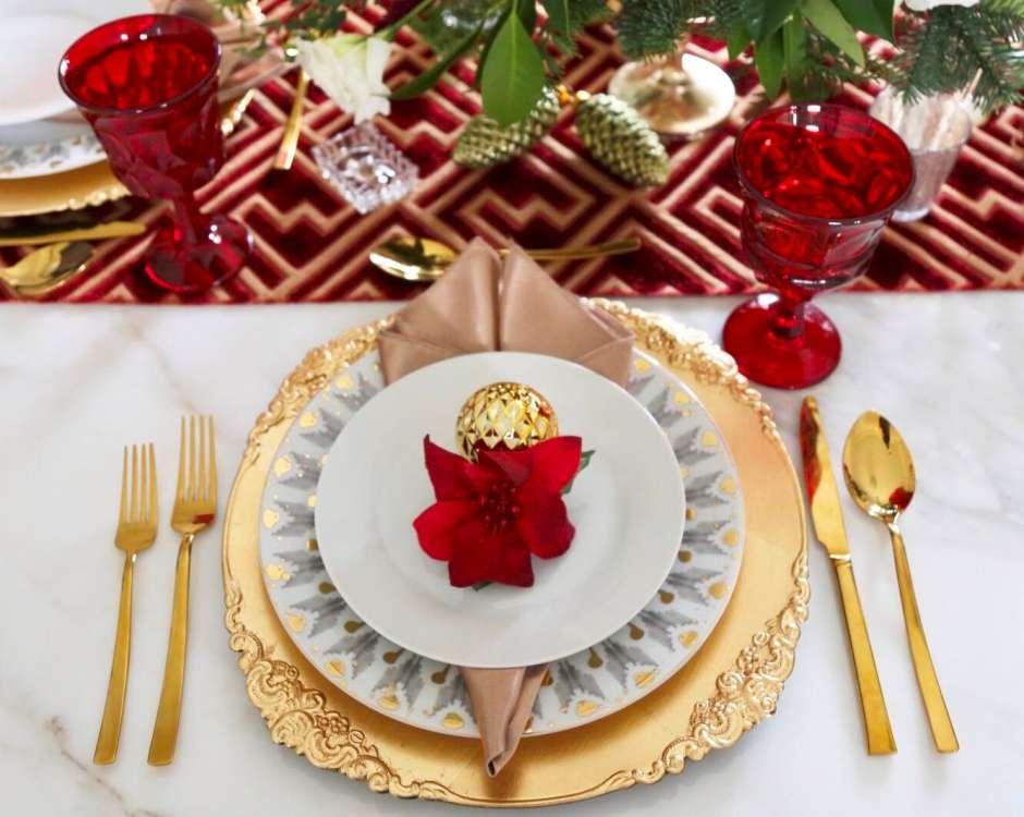 Una simple flor artificial de Poinsettia, acompañada con una bolita navideña, realza la mesa con el espíritu de la Navidad.