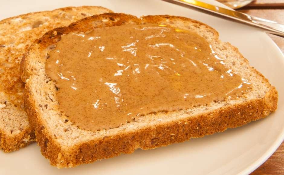 Una rebanada de pan integral embarrada con mantequilla de almendras ayuda a controlar el apetito entre comida y comida.
