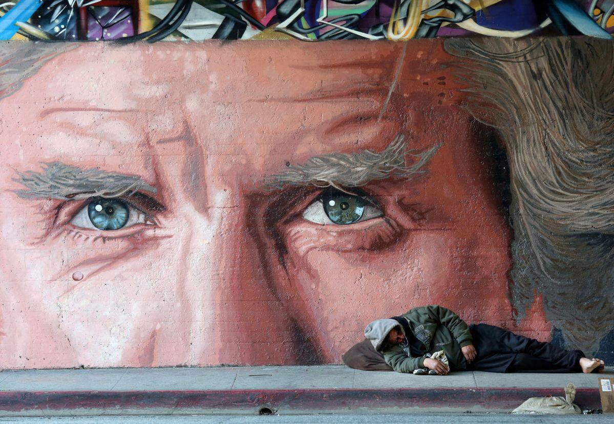 Un hombre sin hogar duerme en Glendale Blvd, bajo el puente de Sunset Blvd. en Los Angeles.