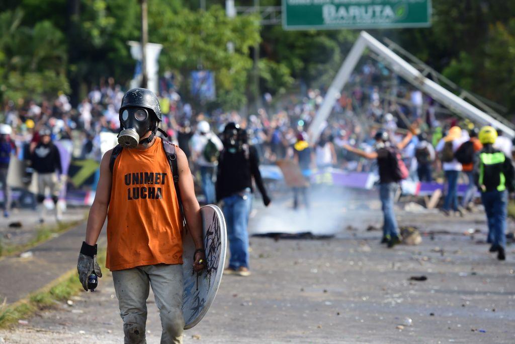 Opositores al gobierno de Maduro chocan con fuerzas antimotines en Caracas.