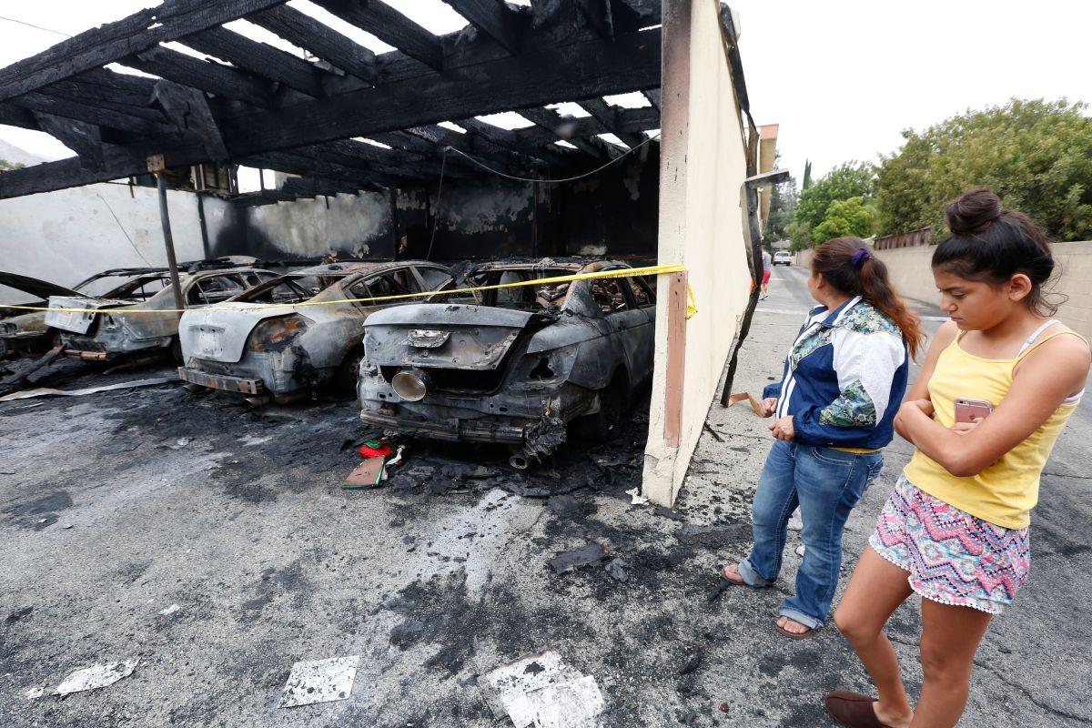 Rubenia Blanco y su hija Yesenia observan los daños provocados por un incendio premeditado en su edificio de apartamentos.  (Aurelia Ventura/La Opinion)