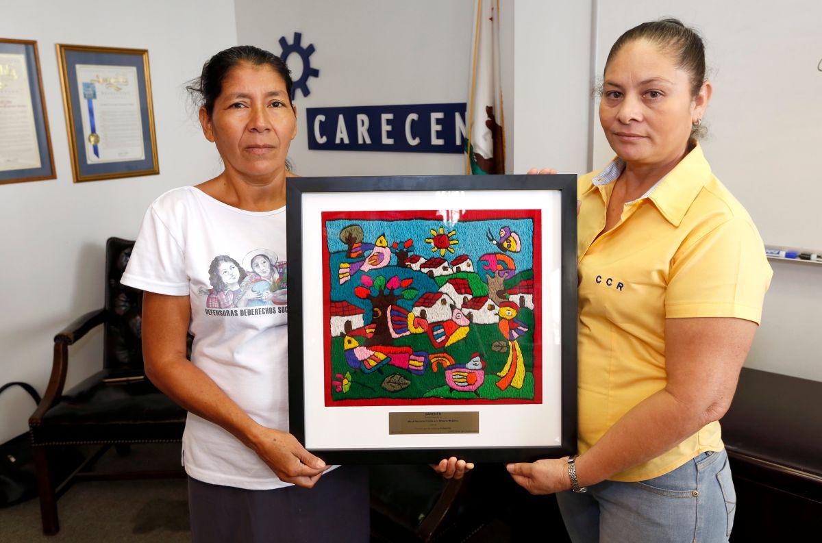 Vidalina Morales y Maria Juventina Ramírez posan con el premio que recibieron por parte de CARECEN en reconocimiento a su lucha en pro del medio ambiente en El Salvador. (Aurelia Ventura/ La Opinion)