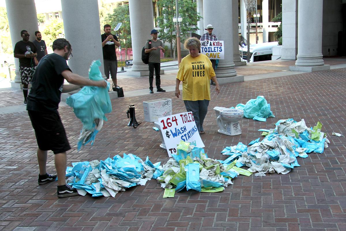 Activistas de Skid Row llevan al ayuntamiento inodoros con mensajes de personas sin hogar