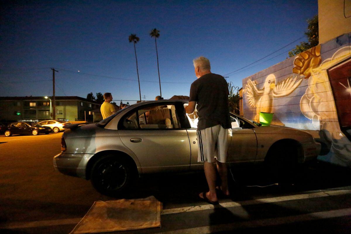 Un hombre que vive en su auto se prepara para pasar la noche en el estacionamiento de la Iglesia Episcopal St. Mary's de Koreatown.   (Aurelia Ventura/La Opinion)
