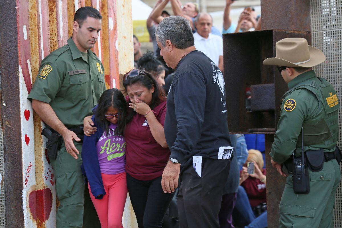 Una madre abraza a su hija en la frontera entre México y EEUU.