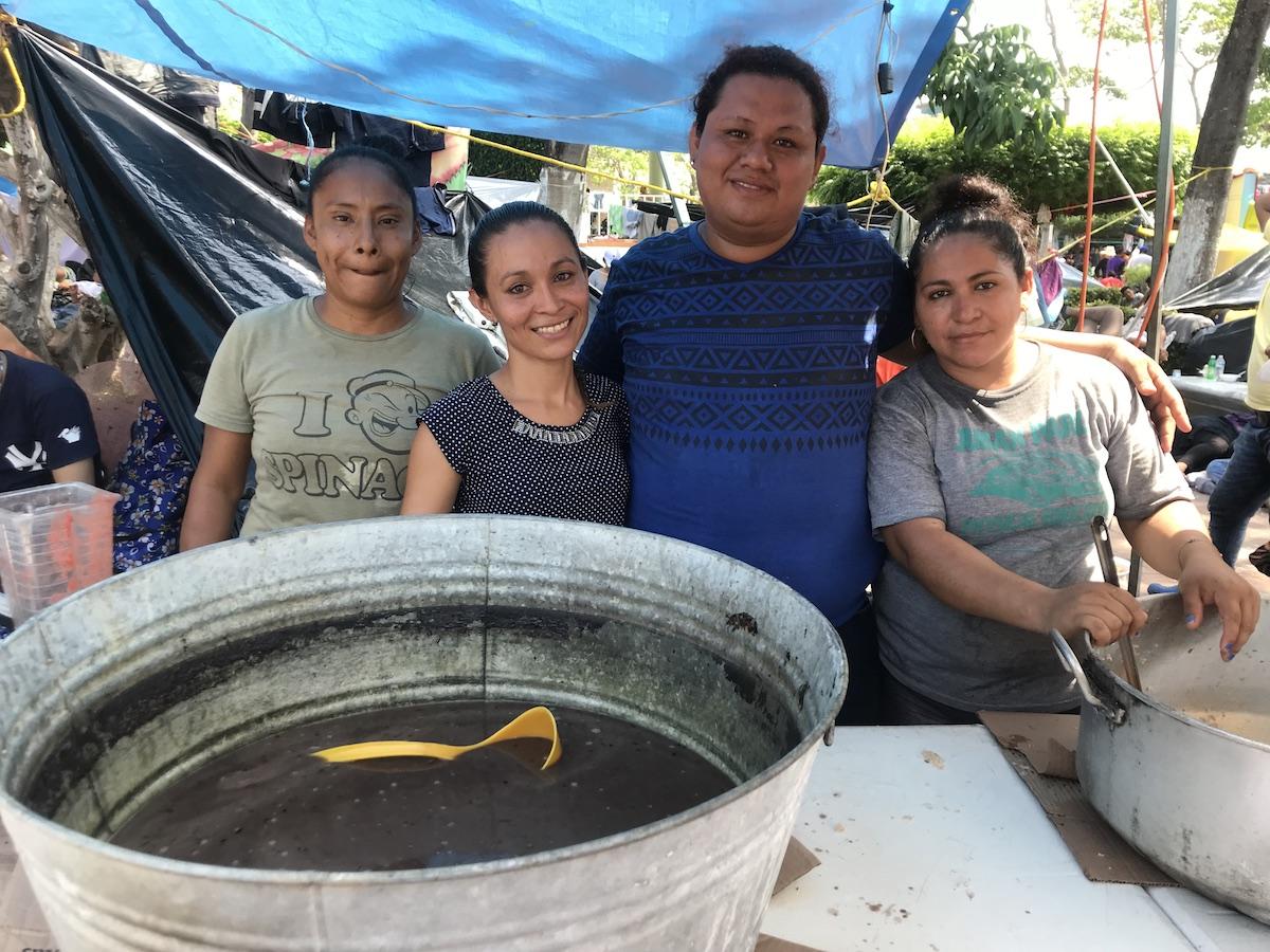 Karla Montes (tercera de d a i) con amigos mexicanos dando comida a migrantes..