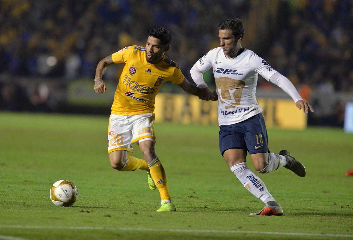 Aquino (i) de Tigres pelea el balón con  Iniestra (d) de Pumas de la UNAM.