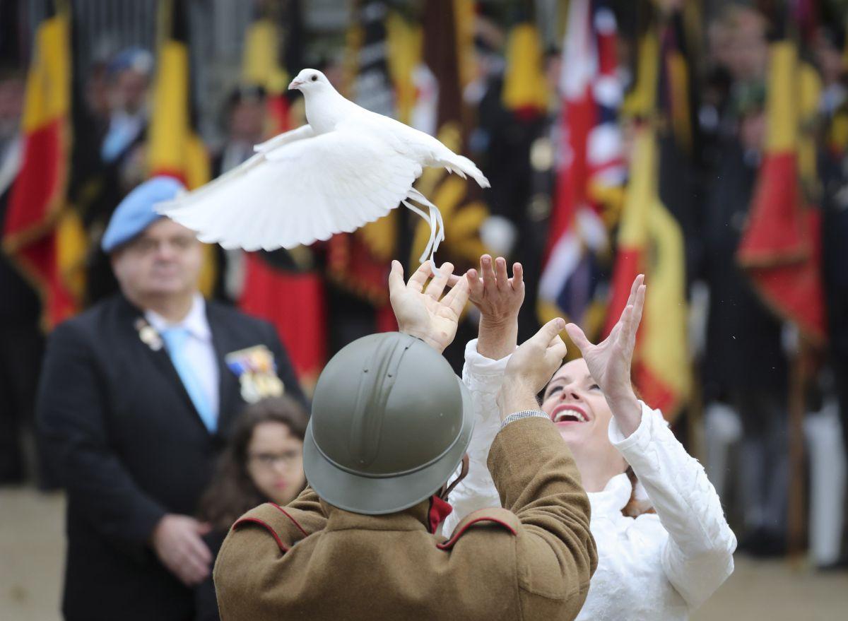 Dos personas lanzan una paloma durante una ceremonia en conmemoración del centenario del Armisticio de la Primera Guerra Mundial del 11 de noviembre de 1918, en la tumba del soldado desconocido en la Columna de Congres, en Bruselas, Bélgica, el 11 de noviembre de 2018, los líderes mundiales se han reunido en Francia para conmemorar el 100 aniversario. del primer armisticio de la guerra mundial, con servicios que tienen lugar en todo el mundo para conmemorar la ocasión. EFE / OLIVIER HOSLET